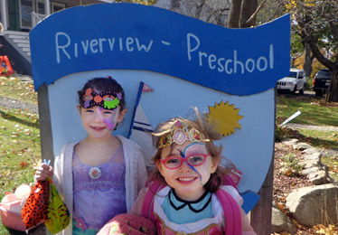 2 girls in front of Riverview Preschool sign